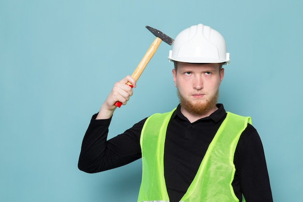 Young man in black shirt and green construction vest holding hammer