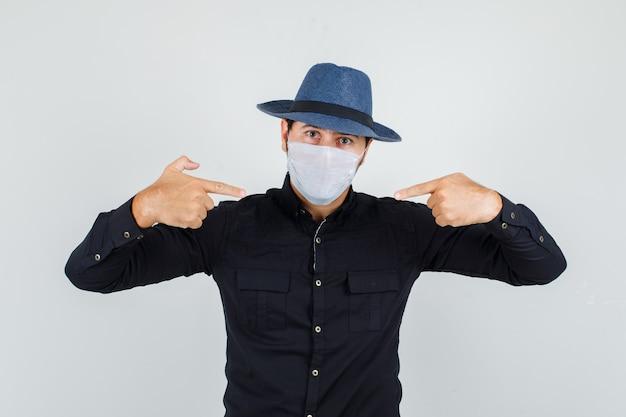 Giovane uomo in camicia nera, cappello che punta alla sua maschera medica