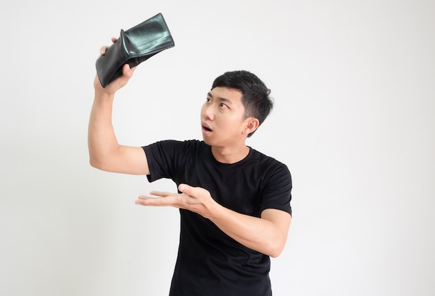 ショック顔でお金を見つけるために手に財布を持って振る若い男の黒いシャツは不幸です