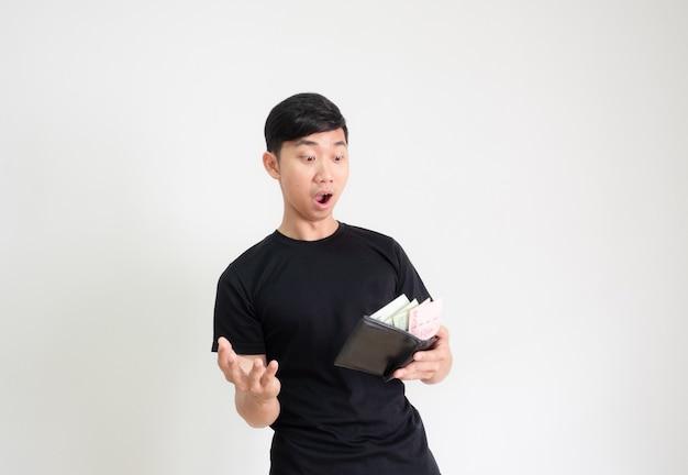 젊은 남자 검은 셔츠 충격과 흰색 절연에 그의 지갑 행복 한 얼굴에 돈을 봐