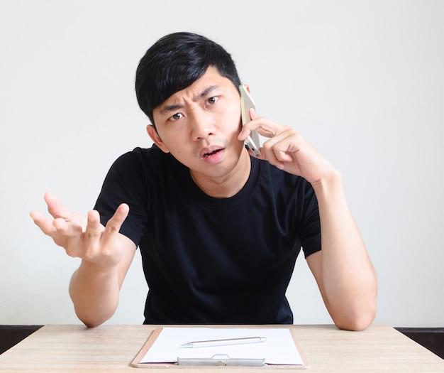젊은 남자 검은 셔츠는 책상에 앉아 전화로 이야기하고 심각하고 혼란스러운 얼굴을 느낀다