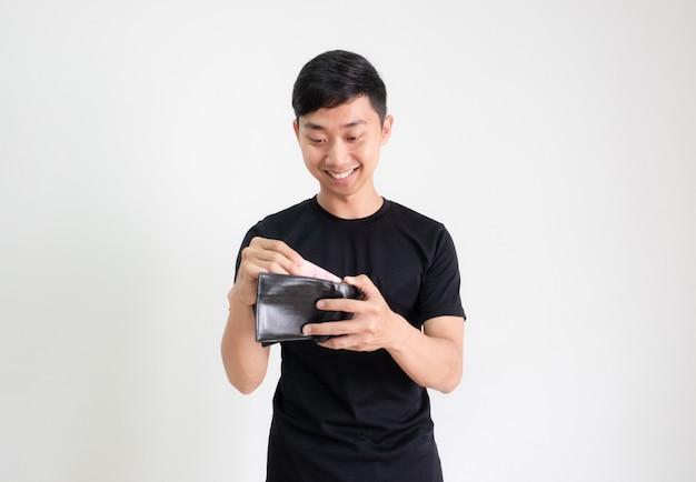 젊은 남자 검은 셔츠는 웃고 행복하고 흰색으로 격리된 지갑에 있는 현금을 봅니다.
