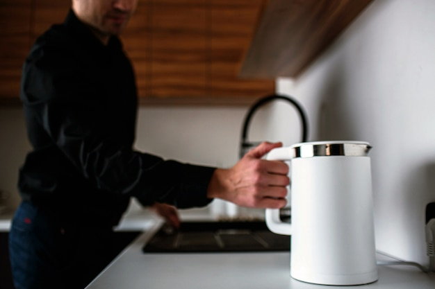 Young man in black shirt stand in kitchen and hold white electric smart kettle