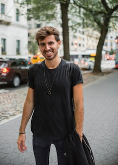 Young man in black smiling on sidewalk