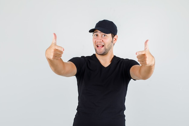 Young man in black t-shirt, cap showing gun gesture and looking cheerful