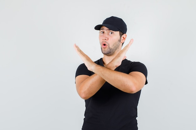 Young man in black t-shirt, cap showing stop gesture and looking excited