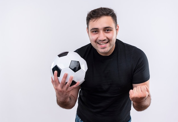 Young man in black t-shirt holding soccer bal l clenching fist happy and excited standing over white wall