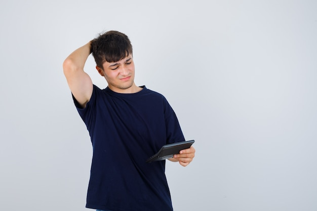 Young man in black t-shirt looking at calculator, keeping hand behind head and looking troubled , front view.