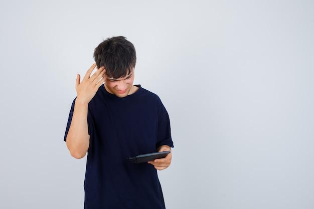 Giovane uomo in maglietta nera guardando la calcolatrice tenendo la mano sulla testa e guardando confuso, vista frontale.