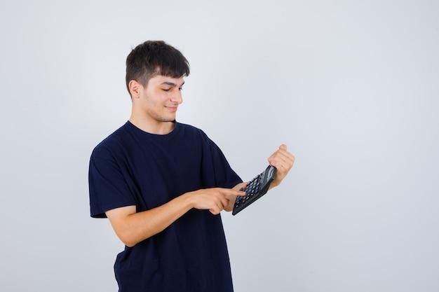 Giovane in maglietta nera che fa i calcoli sulla calcolatrice e che sembra occupato, vista frontale.