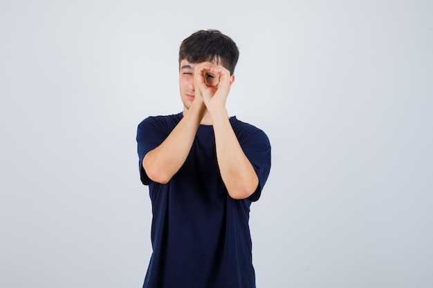 Young man in black t-shirt pretending to peek through hole with his hands and looking curious , front view.