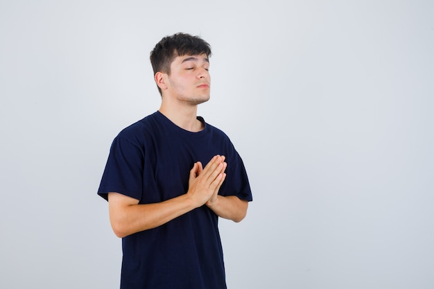 Young man in black t-shirt showing namaste gesture and looking hopeful , front view.