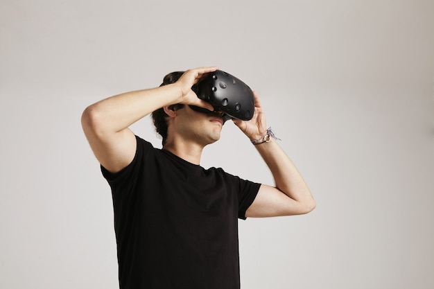 A young man in blank black t-shirt puts on vr glasses isolated on white