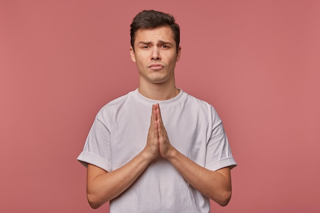 Young man in blank t-shirt, hopes for luck and shows prayer gesture, stands on pink with unhappy expression.