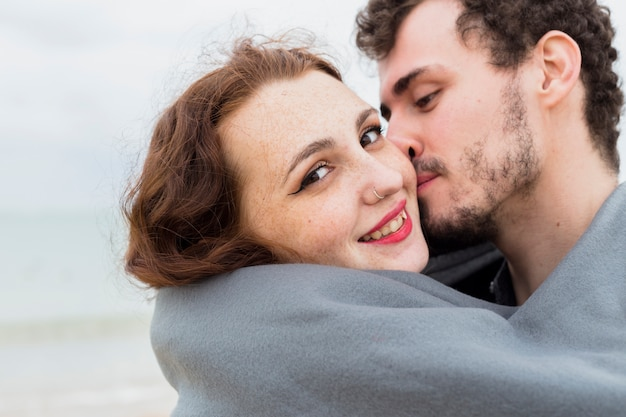 Young man in blanket kissing woman on cheek