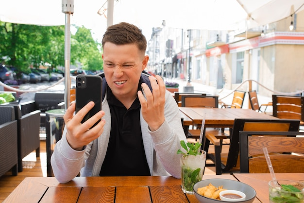 Young man, blogger, sits at table in street cafe, takes selfie on smartphone, or records a video