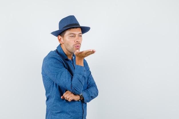 Giovane uomo che soffia aria bacio con labbra imbronciate in camicia blu, cappello, vista frontale.