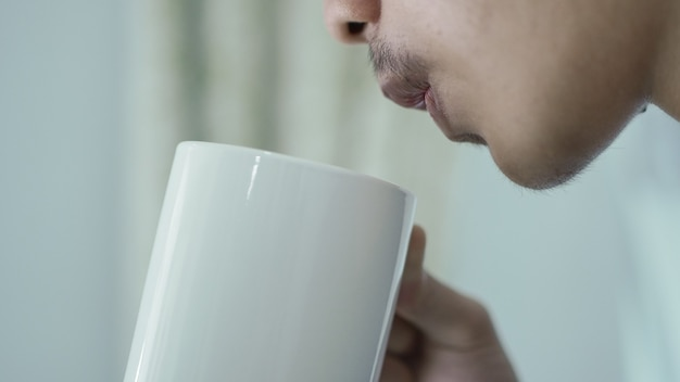 Young man blowing a glass of hot drink at home