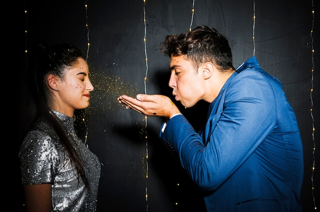 Young man blowing gold glitters at attractive woman