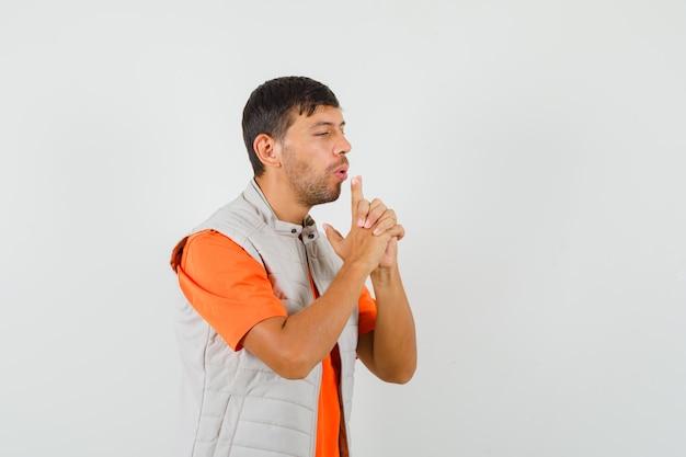 Tシャツ、ジャケット、自信を持って、正面図で指で作られた銃を吹く若い男。