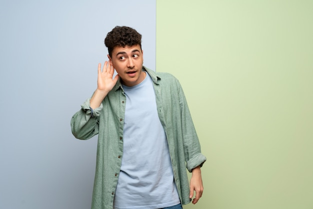 Young man over blue and green background listening to something by putting hand on the ear