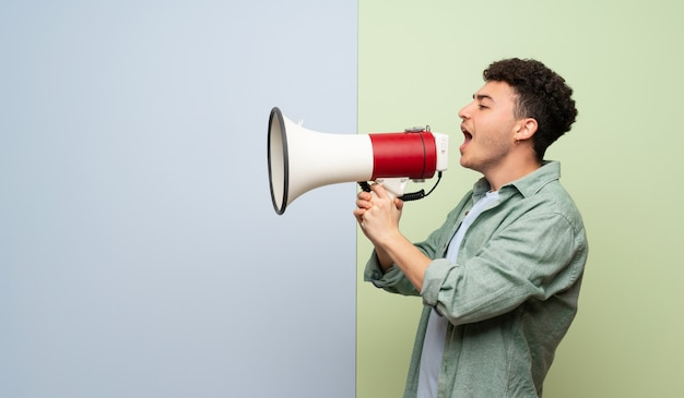 Young man over blue and green background shouting through a megaphone