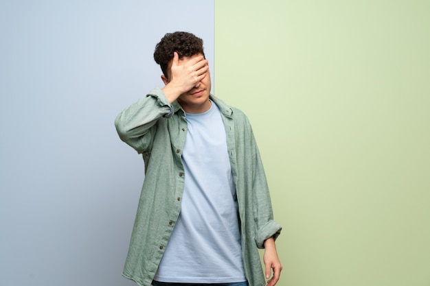 Young man over blue and green covering eyes by hands. do not want to see something