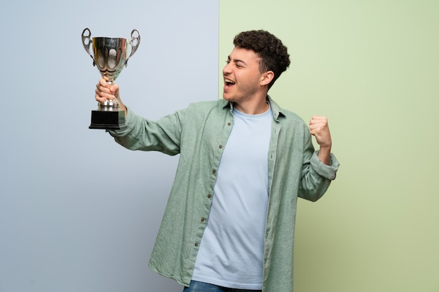 Young man over blue and green holding a trophy