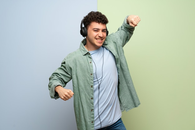 Young man over on blue and on green  listening to music with headphones and dancing