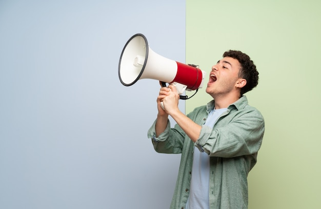 Young man over blue and green shouting through a megaphone