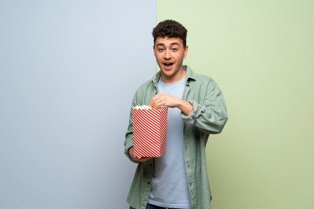 Young man over blue and green  surprised and eating popcorns