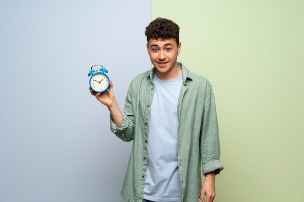 Young man over blue and green wall holding vintage alarm clock