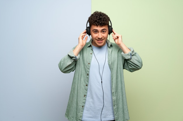 Young man over blue and green wall listening to music with headphones