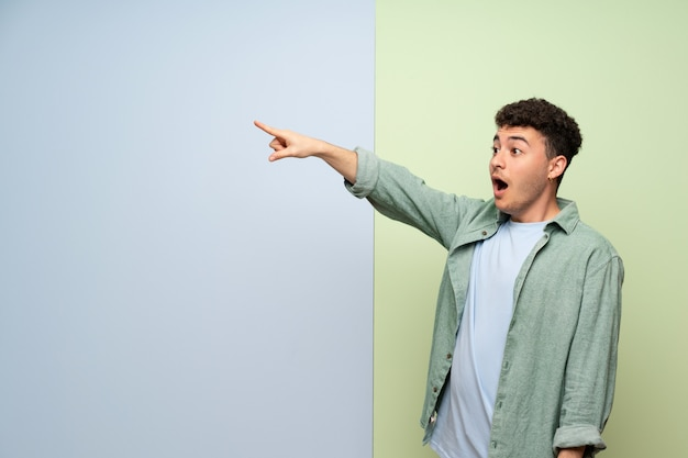 Young man over blue and green wall pointing away