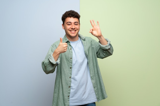 Young man over blue and green wall showing ok sign with and giving a thumb up gesture