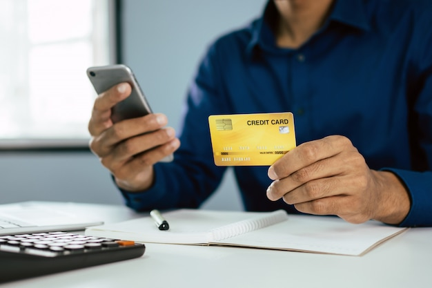 Young man in blue shirt entering security code with mobile phone and paying with credit card