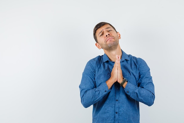 Young man in blue shirt holding hands in praying gesture and looking helpless , front view.