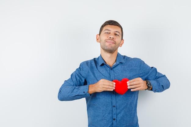 Giovane in camicia blu che tiene cuore rosso e sembra allegro, vista frontale.