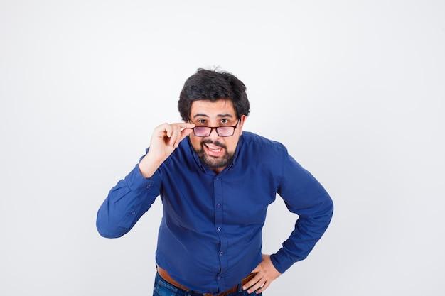 Giovane uomo in camicia blu e jeans che tiene la mano sulla vita mentre si toglie gli occhiali e sembra curioso, vista frontale.