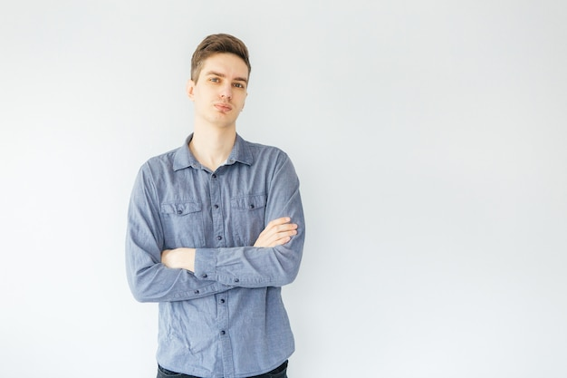 Young man in a blue shirt on a light gray background. worker and entrepreneur