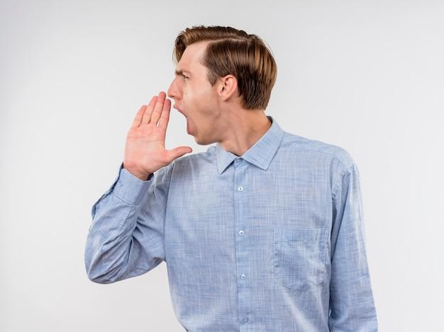 Giovane in camicia blu che osserva da parte gridando con la mano vicino alla bocca che sta sopra il muro bianco