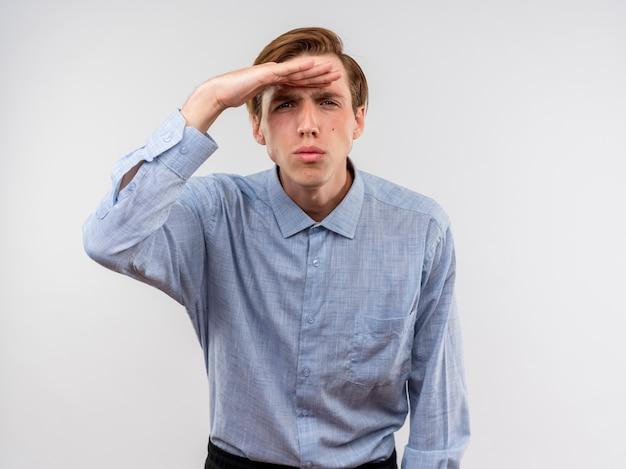 Giovane uomo in camicia blu che guarda lontano con la mano sopra la testa in piedi sul muro bianco