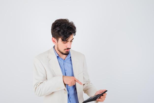 Giovane uomo in camicia blu e giacca bianca che guarda la calcolatrice e la indica e sembra concentrato