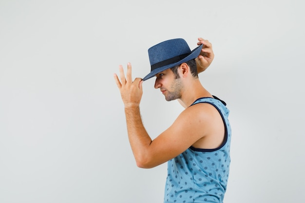 Young man in blue singlet adjusting hat and looking handsome .