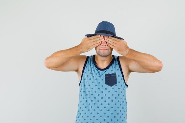 Giovane uomo in canottiera blu, cappello che copre gli occhi con le mani e sembra eccitato