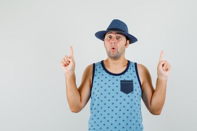 Giovane uomo in canottiera blu, cappello che punta le dita verso l'alto e sembra sorpreso