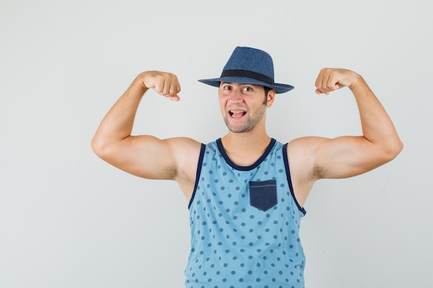 Young man in blue singlet, hat showing muscles of arms and looking powerful