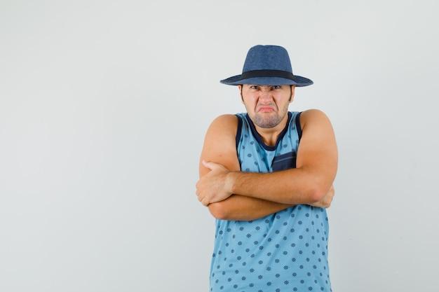 Giovane uomo in canottiera blu, cappello in piedi con le braccia strettamente incrociate e che sembra risentito