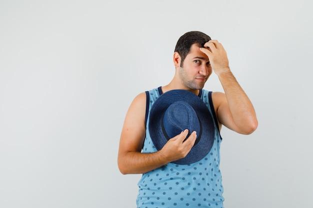 Giovane uomo in singoletto blu che tiene il cappello, pettina i capelli con le dita e sembra elegante