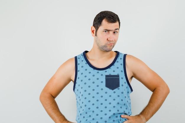 Giovane uomo in singoletto blu che guarda l'obbiettivo mentre accigliato e guardando pensieroso